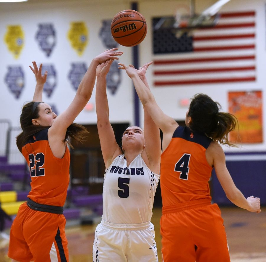 Rolling Meadows' Bridget Rolla (5) stretches for a rebound with Buffalo Grove's Kendra Lee (22) and Macy Floro (4) during Tuesday's girls basketball game in Rolling Meadows.