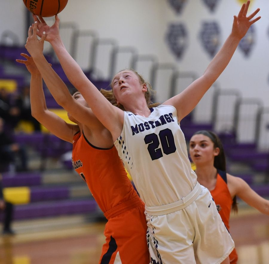 Rolling Meadows' Susannah Holifield (20) reaches for the loose ball during Tuesday's girls basketball game against Buffalo Grove in Rolling Meadows.