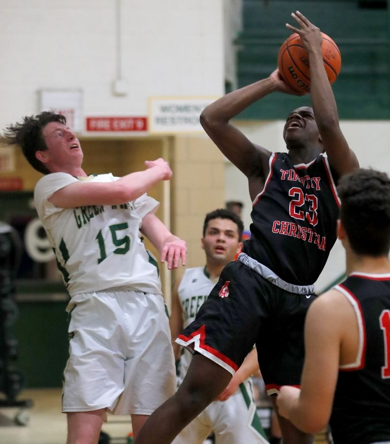 Timothy Christian's Marquis Johnson takes a shot as St. Edward's Aidan Franklin, left, defends in varsity boys basketball in Elgin Tuesday night.