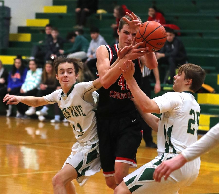 Timothy Christian's Ben VanderWal, center, navigates through traffic including St. Edward's Jacob Breier, left, and Luke Breier, right, in varsity boys basketball in Elgin Tuesday night.