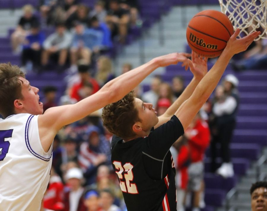 Huntley's Hunter French gets by Hampshire's Nicholas Erickson in varsity boys basketball at Hampshire Wednesday night.