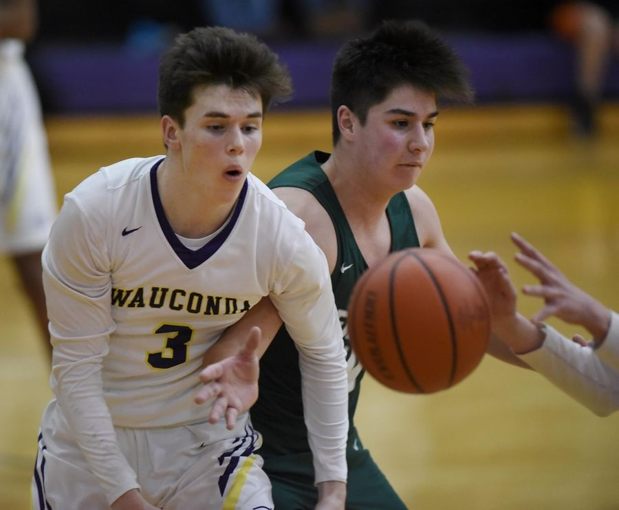 Grayslake Central's Daniel Rogers tries to intercept a pass to Wauconda's Nicholas Bulgarelli in a boys basketball game in Wauconda Thursday.