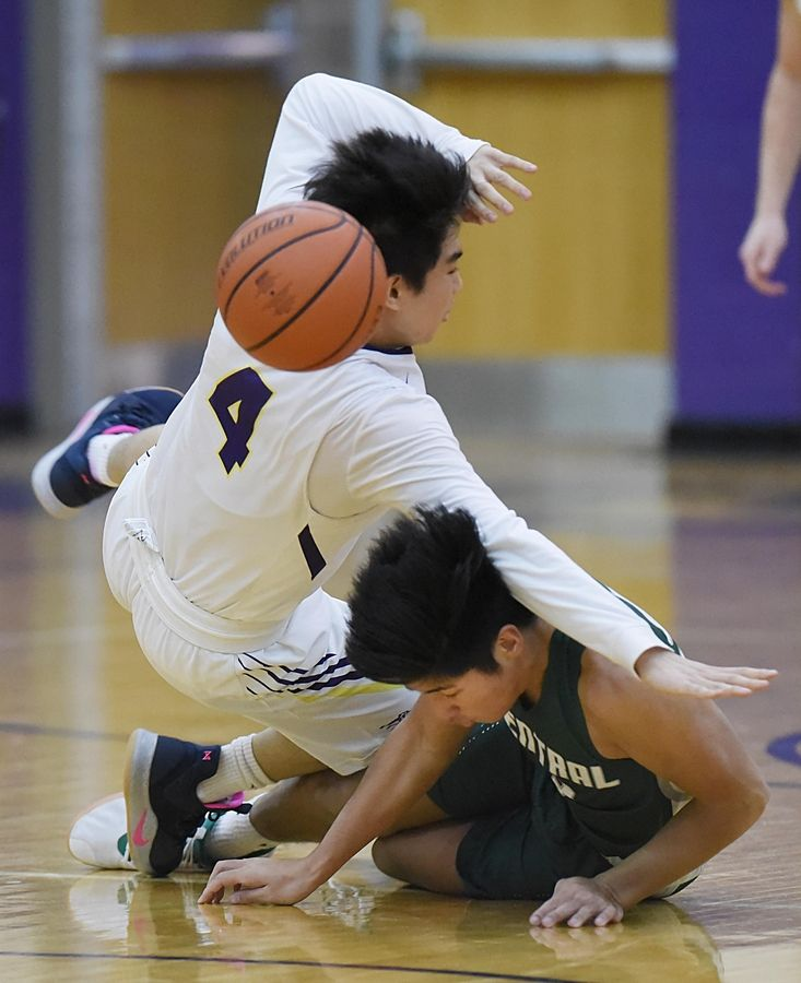 Wauconda's Benjamin Chung falls over Grayslake Central's Dillan Dumanlang in a boys basketball game in Wauconda Thursday.