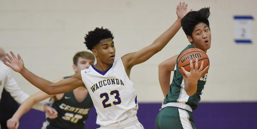 Grayslake Central's Dillan Dumanlang reaches for a loose ball as Wauconda's Donovan Carter guards him in a boys basketball game in Wauconda Thursday.