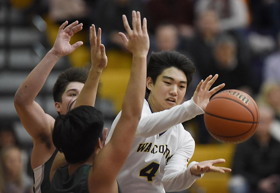 Wauconda's Benjamin Chung passes the ball as Grayslake Central's Dillan Dumanlang and Daniel Rogers block his line to the basket in a boys basketball game in Wauconda Thursday.