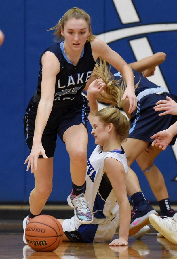 Geneva's Kelly McCloughan falls to the floor as Lake Park's Emma Thorne takes the ball in a basketball game in Geneva Friday.
