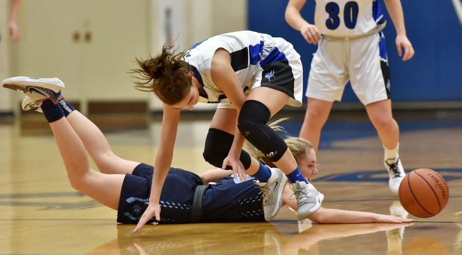 Lake Park's Emma Thorne dives for a loose ball against Geneva's Kate Palmer in a basketball game in Geneva Friday.