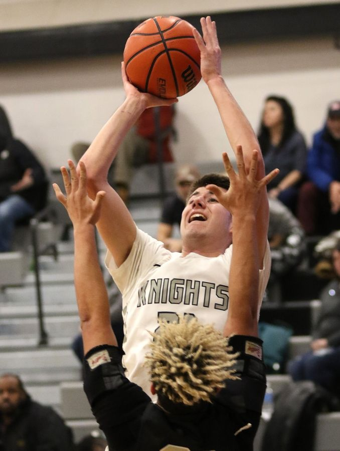 Kaneland senior Bryce Ebert shoots over Sycamore senior Jase Hayes during their game Friday night at Kaneland High School in Maple Park.
