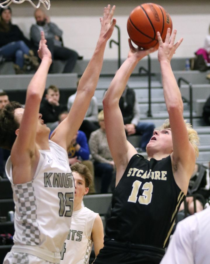 Sycamore sophomore Brody Armstrong shoots over Kaneland senior Will Cushman during their game Friday night at Kaneland High School in Maple Park.