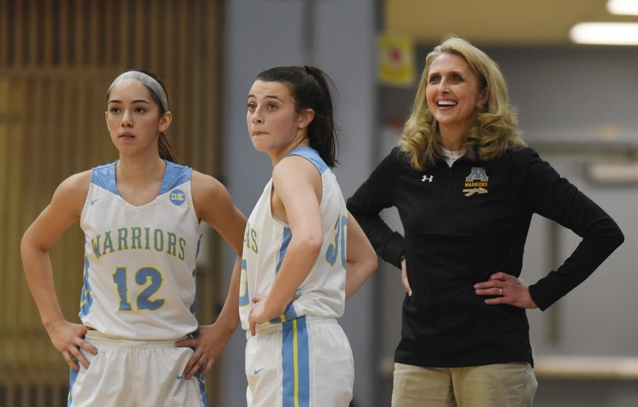 Maine West girls basketball coach Kim de Marigny stands behind players Brianna Hernandez, left, and Lena Albo during Saturday's game against Northwestern High School (IN.) at Willowbrook High School in Villa Park.