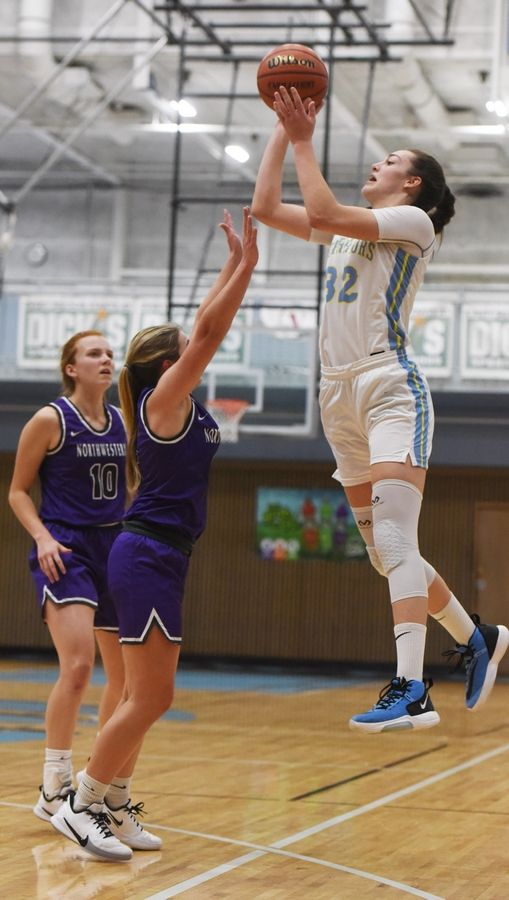 Maine West's Angela Dugalic leaps high on a jump shot defended by Northwestern High School's (IN.) Ellie Boyer, front, and Klair Merrell during Saturday's game at Willowbrook High School in Villa Park.
