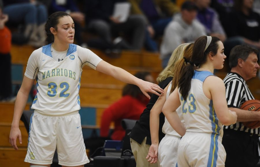Maine West's Angela Dugalic, left, pats her teammates on the back after fouling out during Saturday's game against Northwestern High School (IN.) at Willowbrook High School in Villa Park.