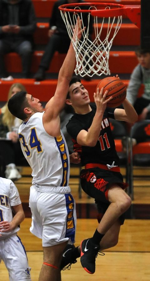 Wheaton Warrenville South's Evan England soars past Warren's Adnan Sarancic at the Orange and Black Gym in the 8th Annual Wheaton Warrenville South MLK Tournament in varsity boys basketball Monday night.