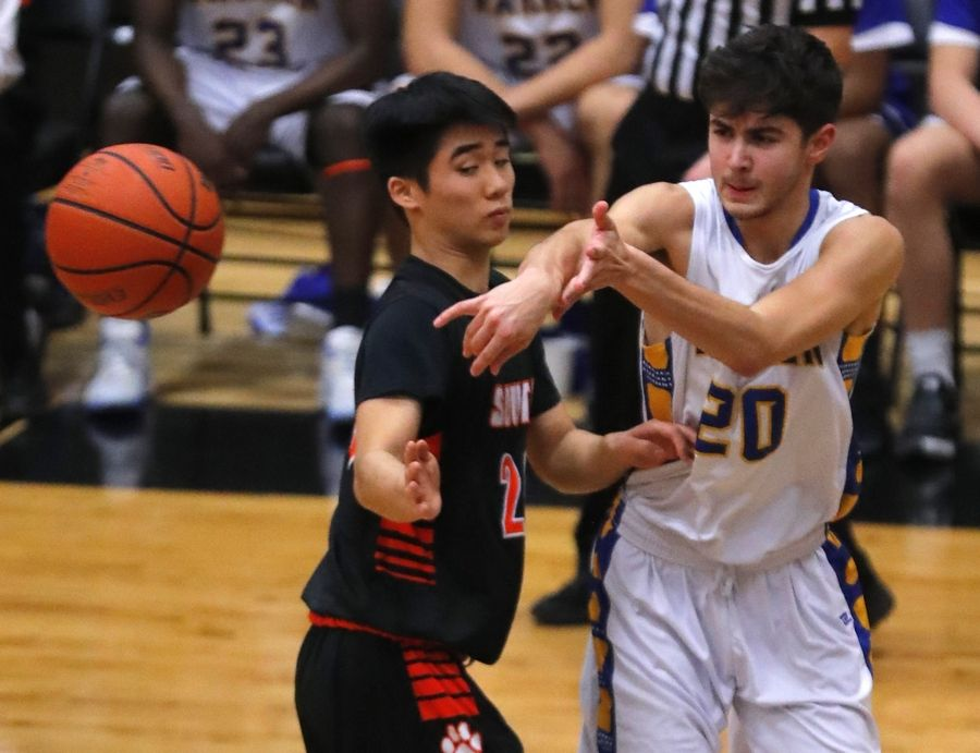 Wheaton Warrenville South's Micah Kim, left, guards Warren's Alexander Figueroa at the Orange and Black Gym in the 8th Annual Wheaton Warrenville South MLK Tournament in varsity boys basketball Monday night.
