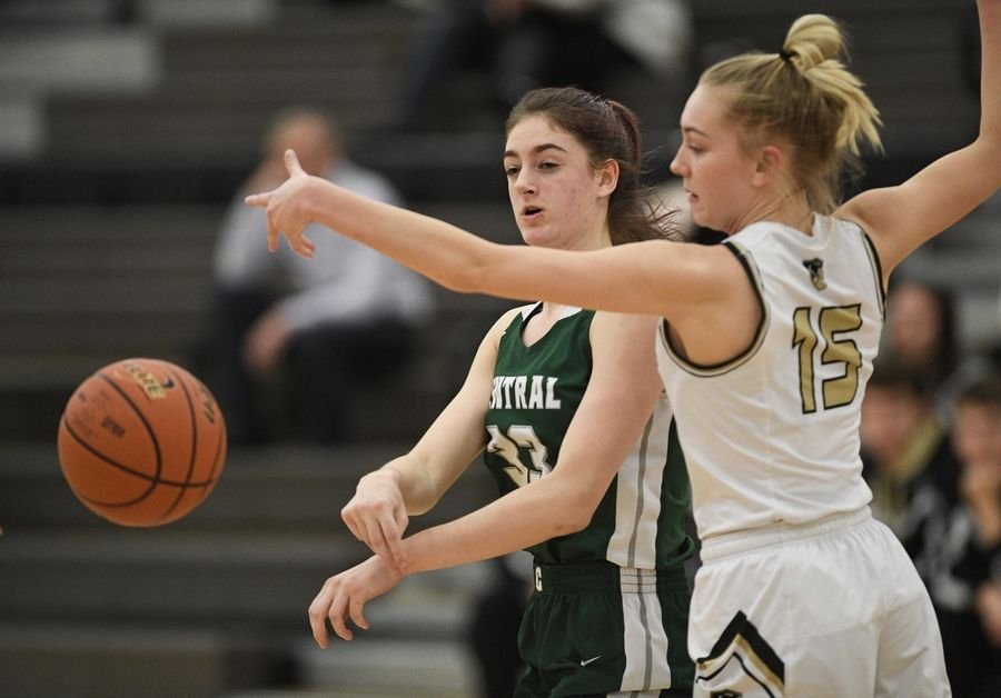 Grayslake Central's Kate Bullman passes around Grayslake North's Grace Wamser in a girls basketball game at Central High School Wednesday.