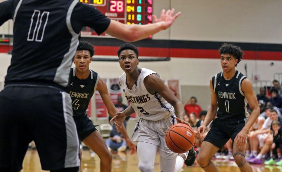 Rolling Meadows' Orlando Thomas drives toward the basket against Fenwick during the When Sides Collide Shootout at Glenbard East on Jan 25. The Mustangs lost 69-56.