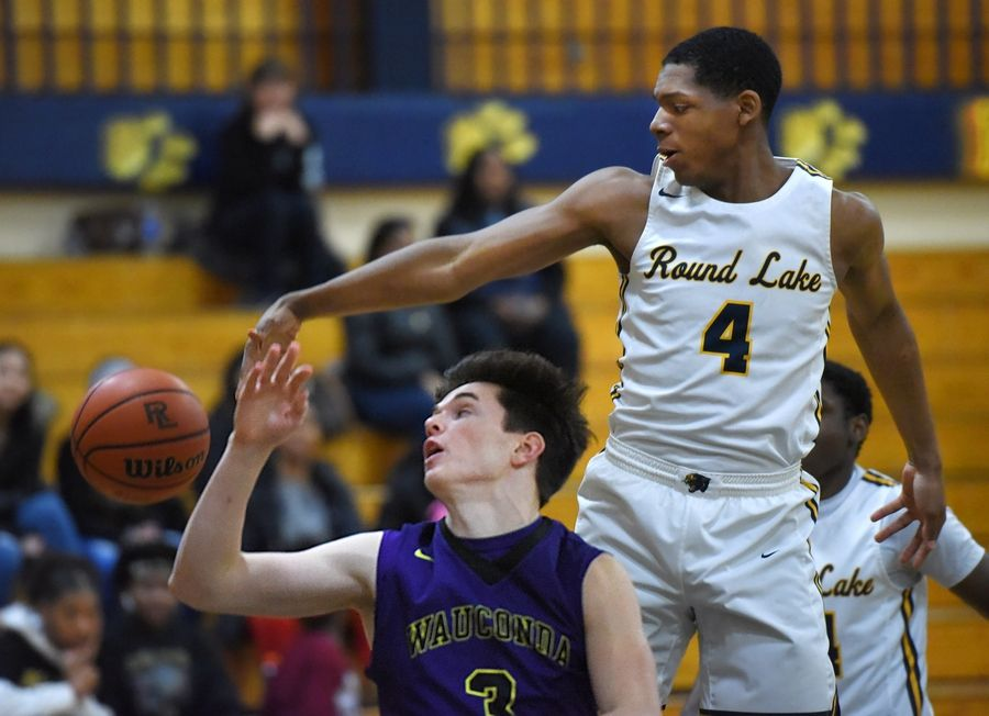 Round Lake's Hakim Williams blocks a shot by Wauconda's Nick Bulgarelli in a boys basketball game in Round Lake Tuesday.