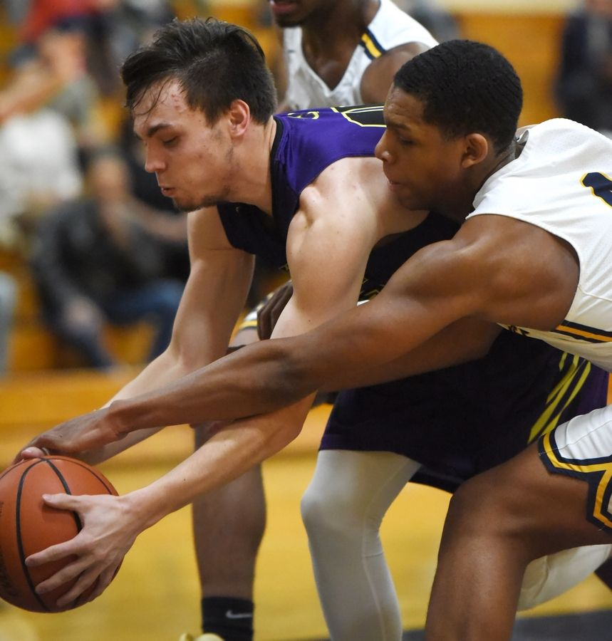 Wauconda's Jake Shanholtzer and Round Lake's Hakim Williams reach for the ball in a boys basketball game in Round Lake Tuesday.