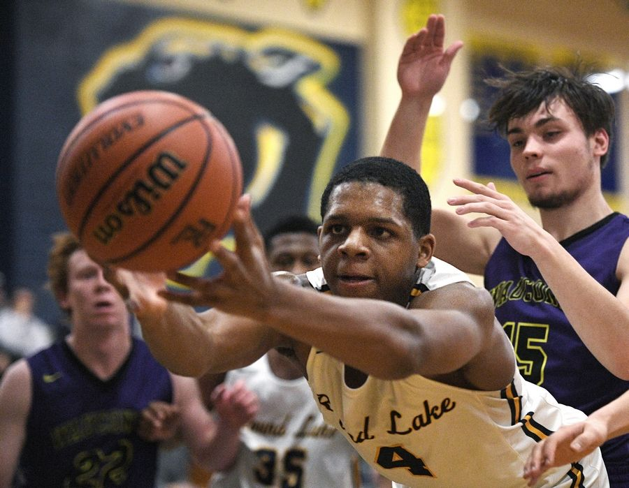 Round Lake's Hakim Williams stretches to keep the ball from going out of bounds against Wauconda in a boys basketball game in Round Lake Tuesday.