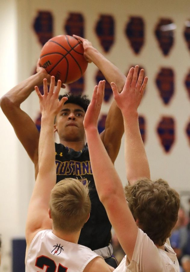 Rolling Meadows' Max Christie shoots through traffic at Buffalo Grove in varsity boys basketball Friday. Christie scored 42 points as the Mustangs won 93-83 in double overtime.