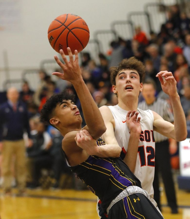 Rolling Meadows' Max Christie, left, tangles with Buffalo Grove's Kam Craft in varsity boys basketball Friday.