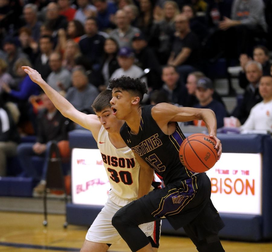 Rolling Meadows' Max Christie moves the ball as Buffalo Grove's Sloan Kipley keeps pace in varsity boys basketball Friday.