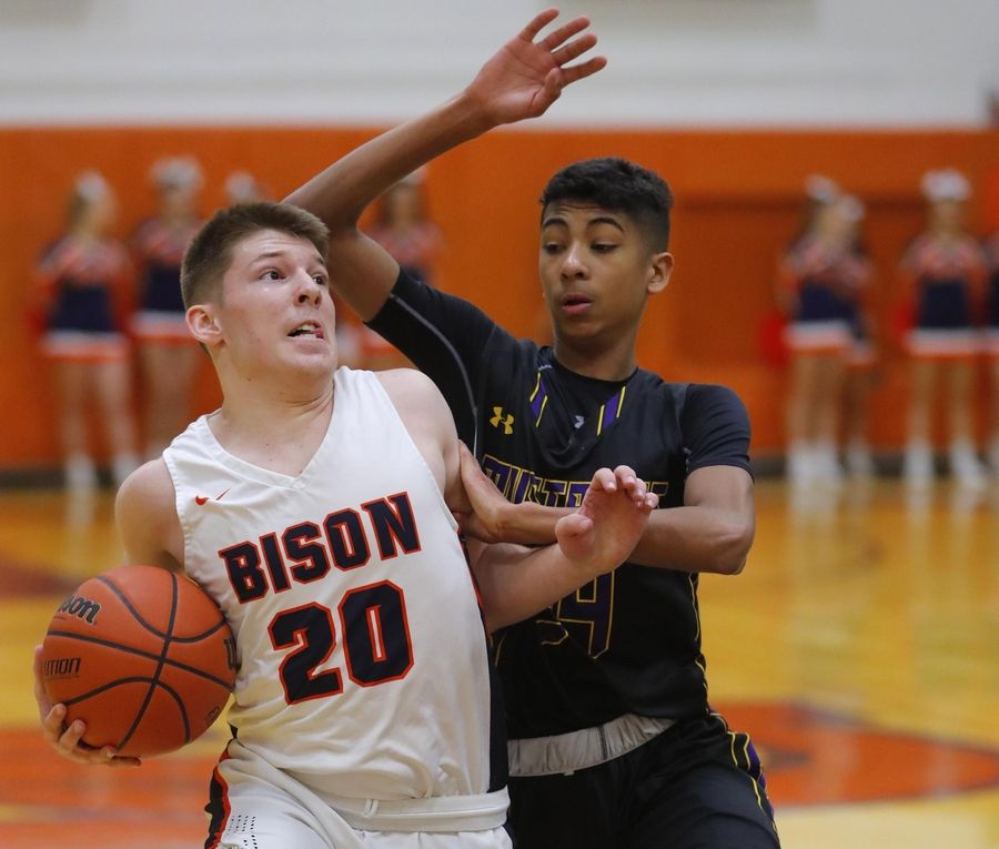 Rolling Meadows' Cameron Christie, right, defends as Buffalo Grove's Tyler Kipley drives to the hoop in varsity boys basketball Friday.