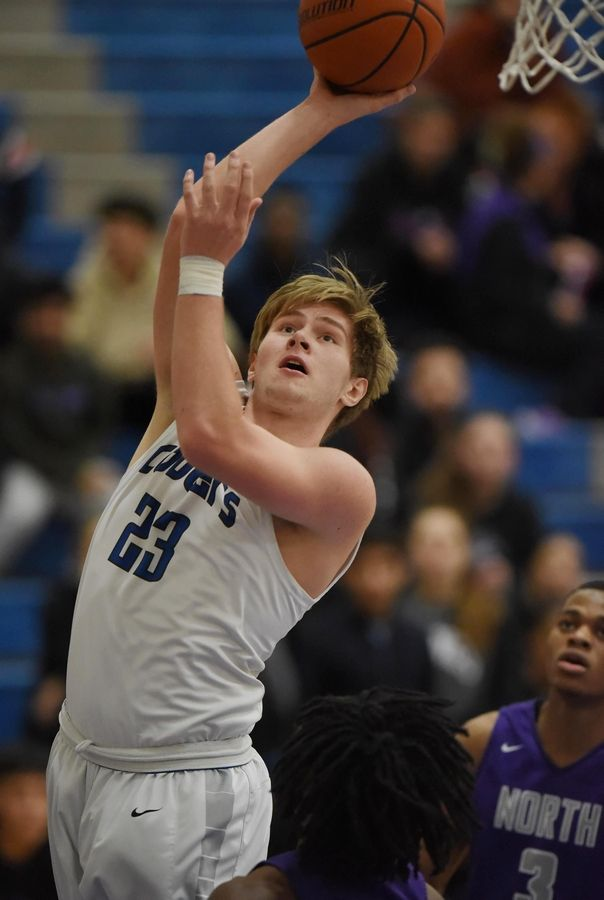 Vernon Hills' Jack Barszcz scores over Niles North's Lennox Manroe in a boys basketball game in Vernon Hills Friday.
