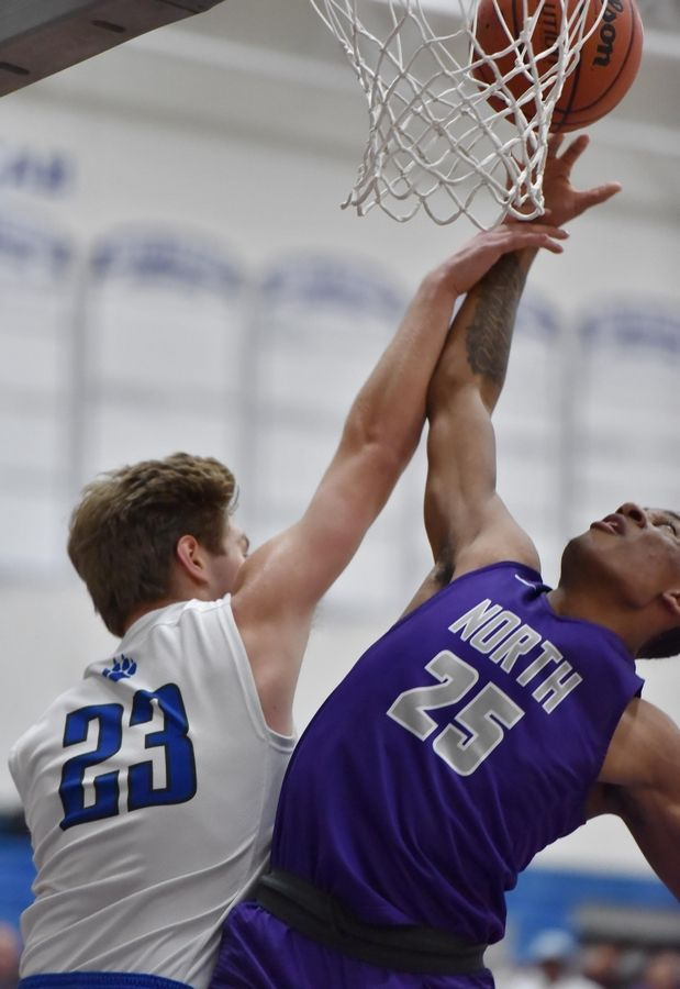 Niles North's Jalen Butler and Vernon Hills' Jack Barszcz stretch for a rebound in a boys basketball game in Vernon Hills Friday.