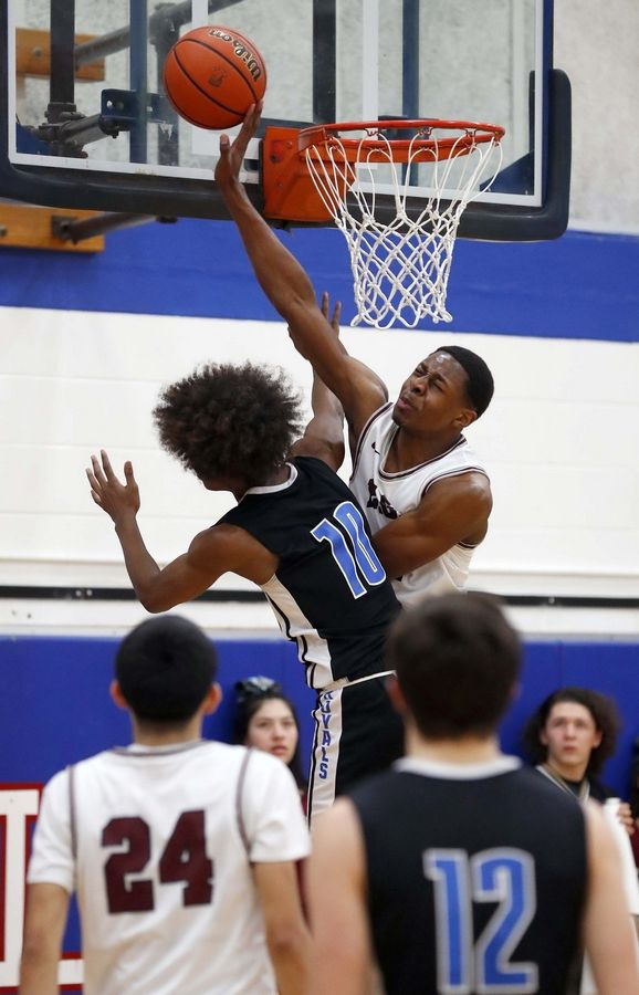 Larkin's Damari Wheeler-Thomas (10) goes to the hoop as Elgin's Jeffery Lomax (1) gets a block and a foul Friday during the crosstown game in Elgin.