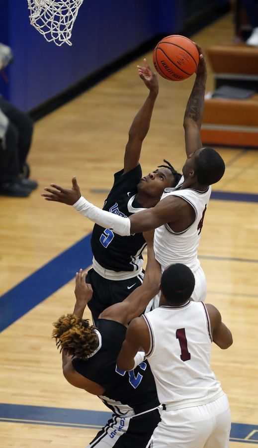 Larkin's Jamarion Stubbs (5) and Elgin's DionT Rodgers (4) battle at the basket Friday during the crosstown game in Elgin.