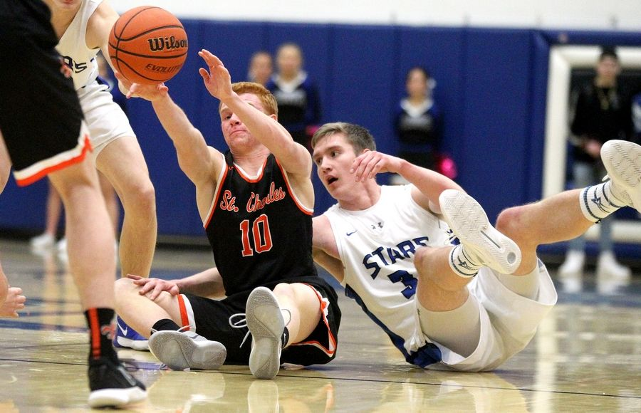 St. Charles East's Andrew Risberg (10) passes the ball away from St. Charles North's Connor Linke during a game at North on Feb. 14.