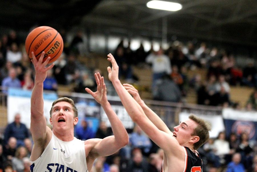 St. Charles North's Connor Linke (left) gets the ball up during a home game against St. Charles East on Feb. 14.