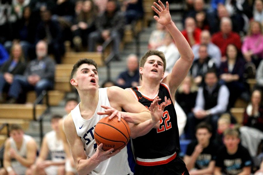 Ethan Marlowe of St. Charles North tries to get the ball past St. Charles East's Zack Clodi during a game at North on Feb. 14.