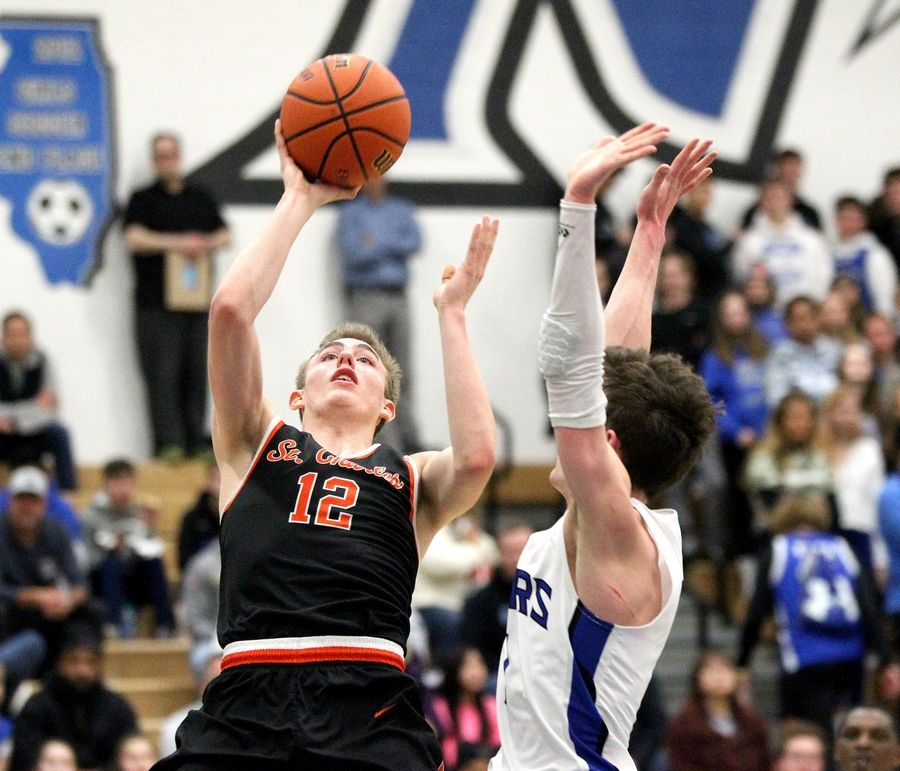 St. Charles East's Thomas Ditsworth (12) shoots the ball past the defense of St. Charles North's Luke Scheffers during a game at St. Charles North on Feb. 14.