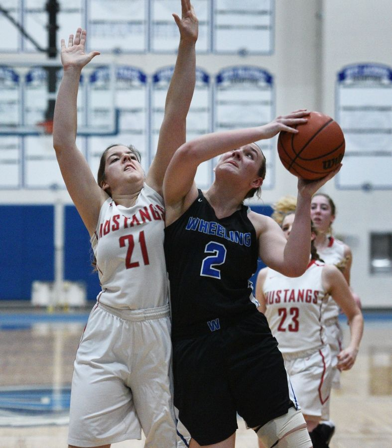 Wheeling's Morgan Collar (2) goes up for a shot under pressure from Mundelein's Ava Vogt (21) during Monday's Class 4A regional girls basketball game in Lake Zurich.