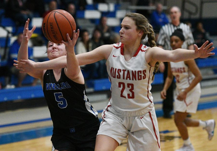 Wheeling's Sophia Stanke (5) gets to a rebound before Mundelein's Lauryn Webb (23) during Monday's Class 4A regional girls basketball game in Lake Zurich.