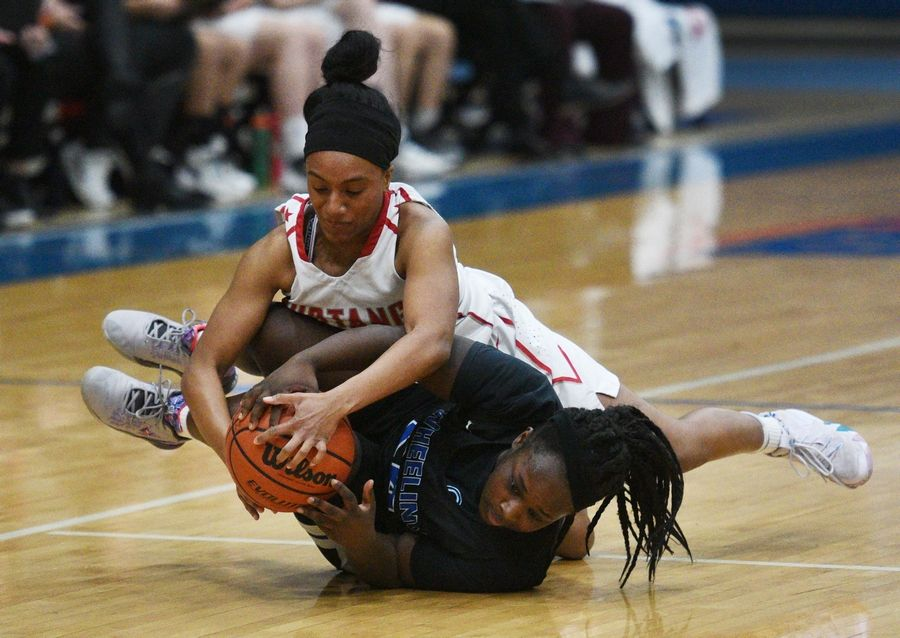 Mundelein's Damia Ali (top) and Wheeling's Naomi Metellus get wrapped up running down a loose ball during Monday's Class 4A regional girls basketball game in Lake Zurich.