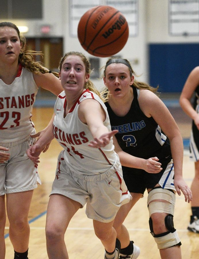 Mundelein's Allison Binz stretches for a rebound ahead of Wheeling's Morgan Collar (2) during Monday's Class 4A regional girls basketball game in Lake Zurich.