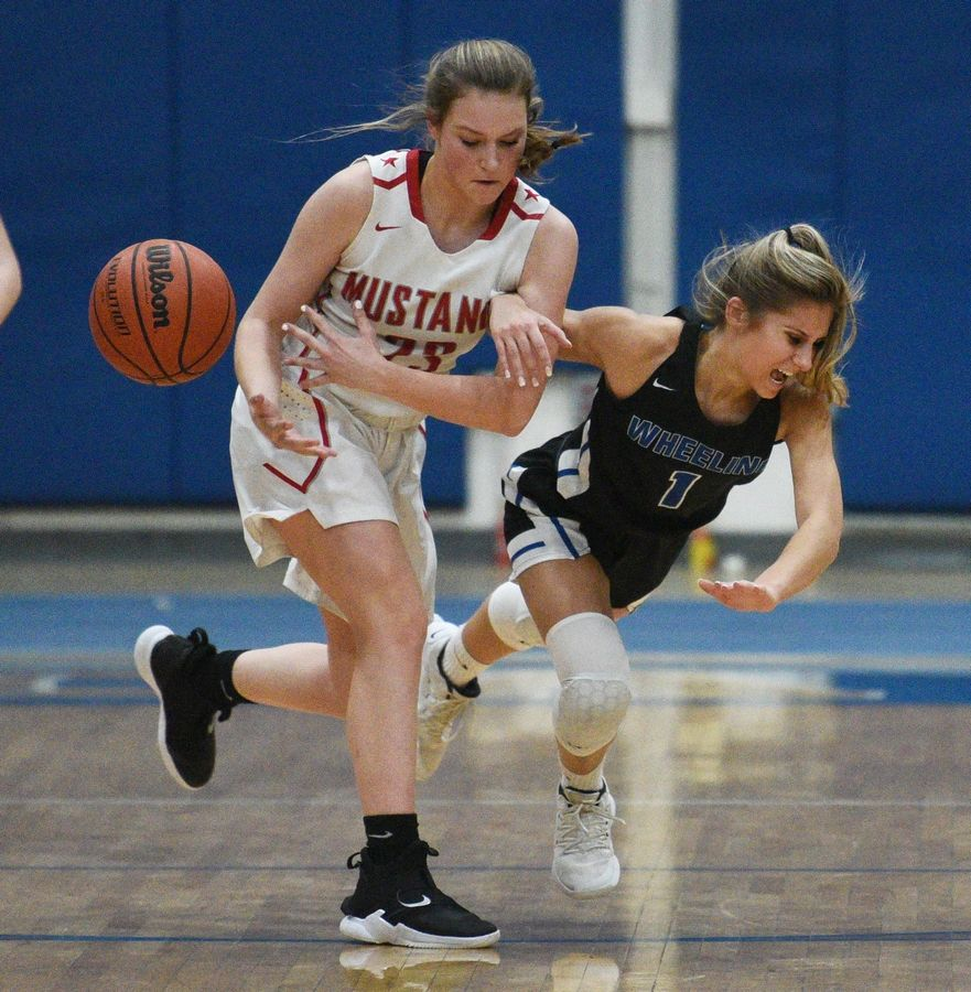 Mundelein's Tess McKay, left, knocks the ball away from Wheeling's Chloe Drozdz (1) during Monday's Class 4A regional girls basketball game in Lake Zurich.