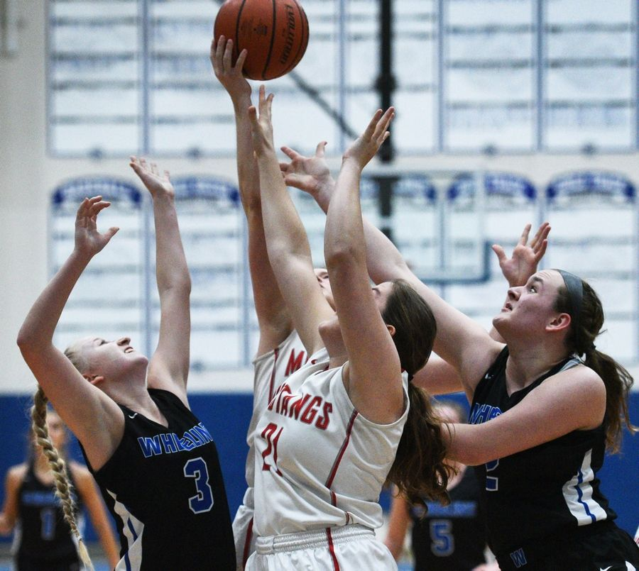 Wheeling's Nicole Niznik (3) and Morgan Collar (2) attempt the rebound with Mundelein's Ava Vogt (21) during Monday's Class 4A regional girls basketball game in Lake Zurich.