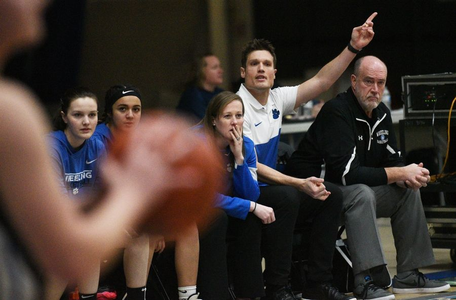 Wheeling's Matt Weber, second from right, coaching from the bench during Monday's Class 4A regional girls basketball game against Mundelein in Lake Zurich.