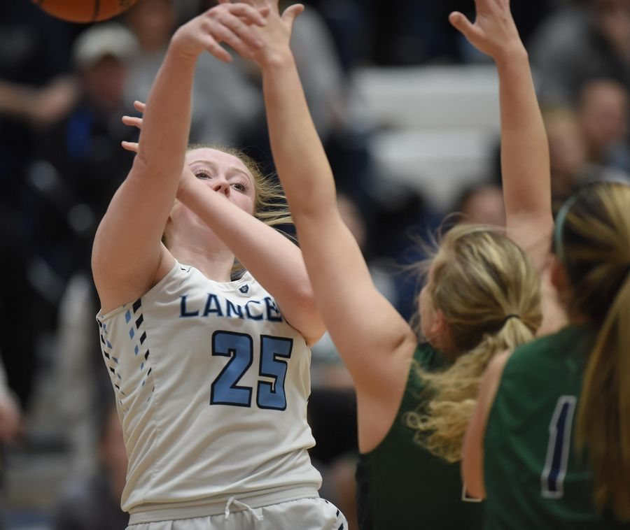 Lake Park's Ellie Helm passes under pressure from Bartlett's Alexis Sinclair in the Class 4A Lake Park girls basketball regional final game in Roselle Thursday.