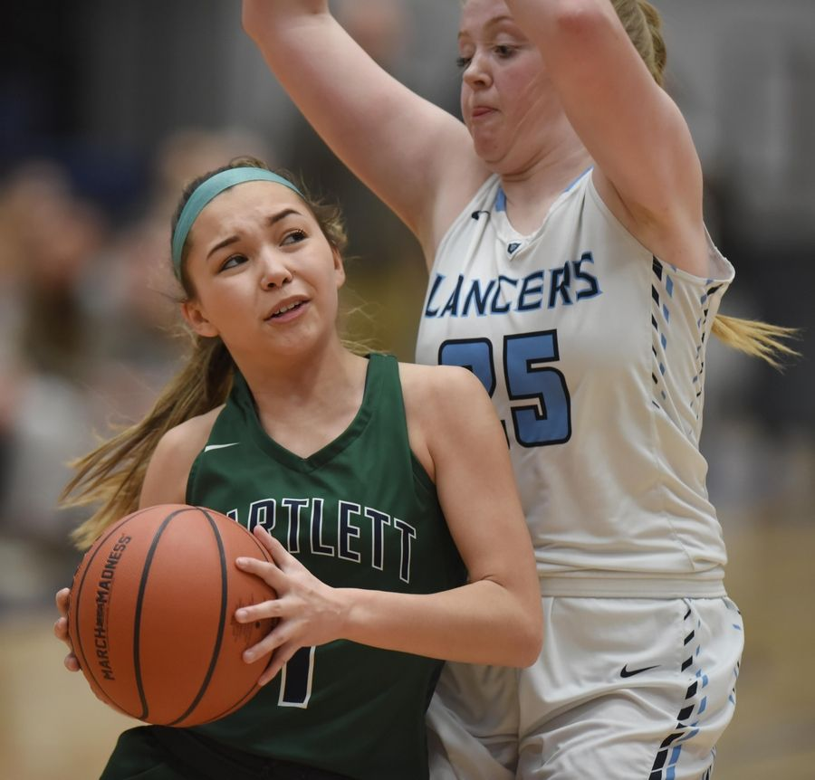 Bartlett's Mackenzie Hare leans into Lake Park's Ellie Helm in the Class 4A Lake Park girls basketball regional final game in Roselle Thursday.
