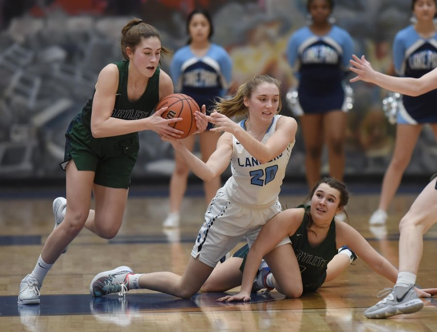 Bartlett's Kylie Walker steals the ball from Lake Park's Emma Thorne as she tangles with Bartlett's Danielle Hedeen in the Class 4A Lake Park girls basketball regional final game in Roselle Thursday.