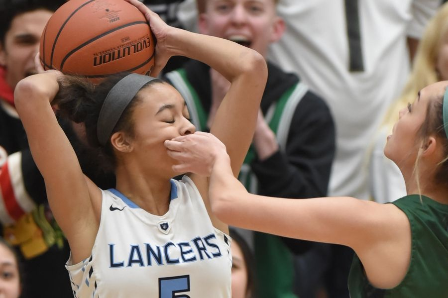 Lake Park's Gabi Burgess is swiped across the face by Bartlett's Trinity Reyes in the Class 4A Lake Park girls basketball regional final game in Roselle Thursday.