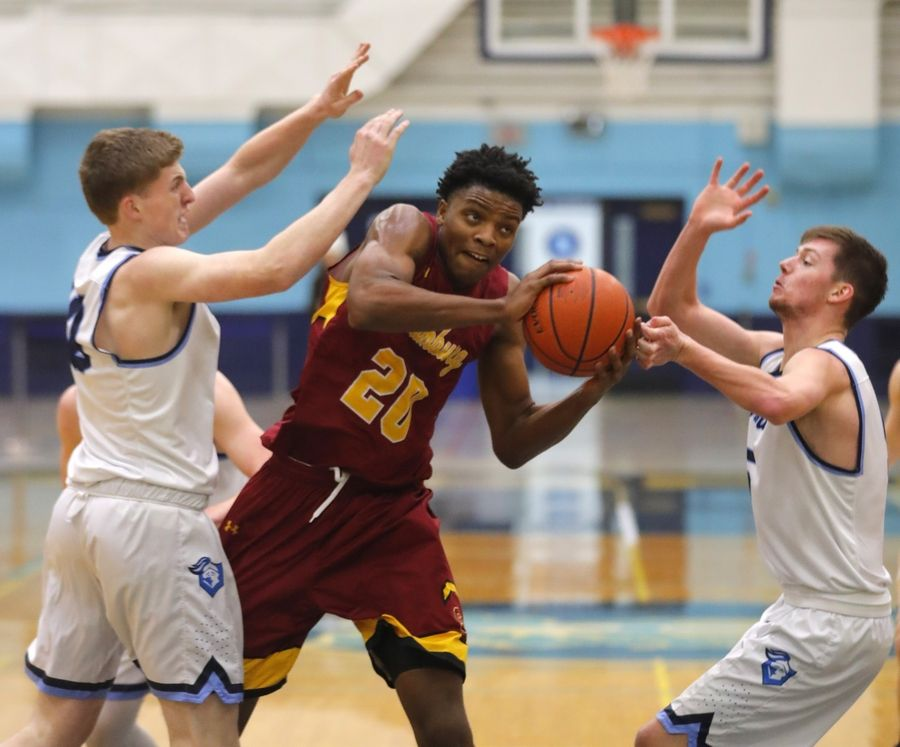 Schaumburg's Chris Hodges fights his way to the hoop as Prospect's Colin Carroll, left, and Matthew McAleer, right, defend earlier this season.
