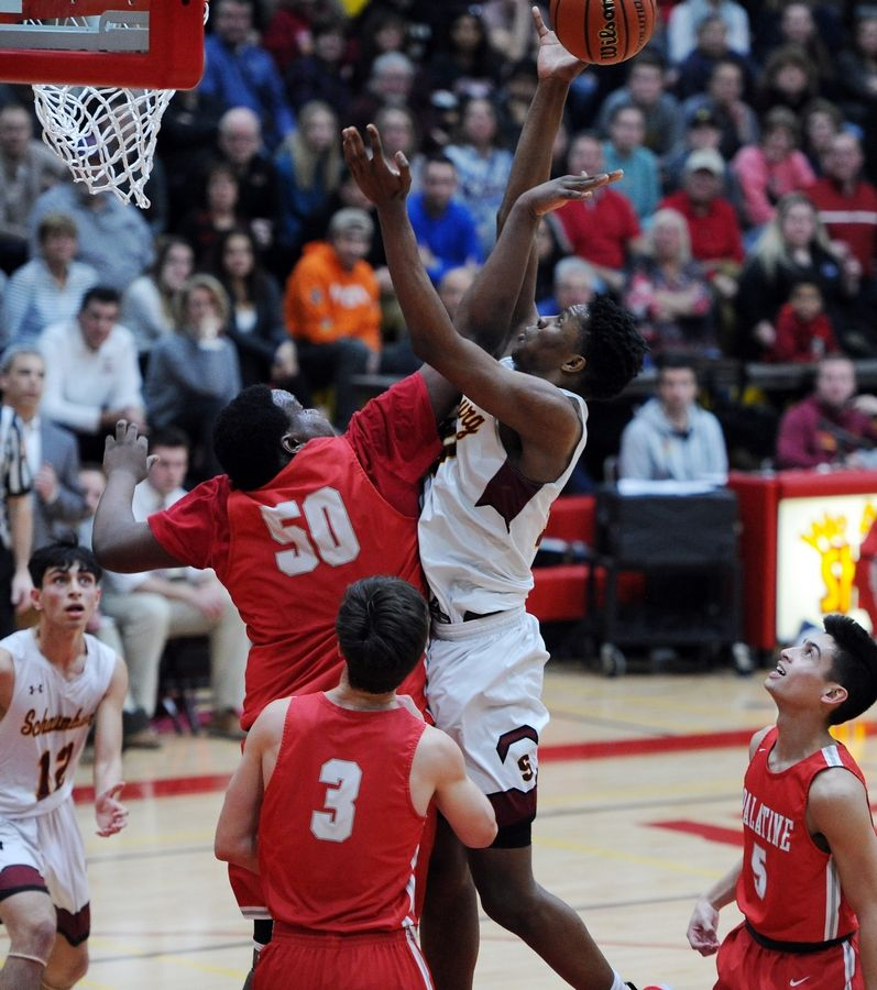 Schaumburg's Chris Hodges goes up against Palatine's Julian Campbell in the varsity basketball matchup at Schaumburg on Friday.