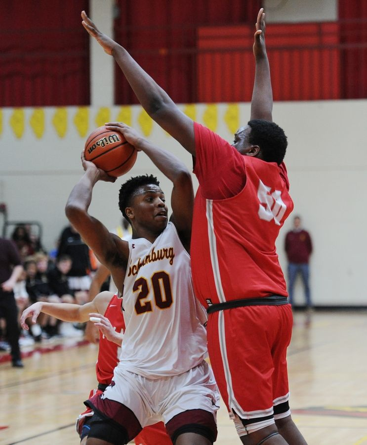 Schaumburg's Chris Hodges goes up against Palatine's Julian Campbell under the basket in the varsity basketball matchup at Schaumburg on Friday.