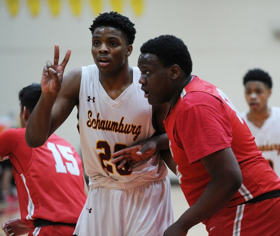 Schaumburg's Chris Hodges and Palatine's Julian Campbell keep a close eye on each other in the varsity basketball matchup at Schaumburg on Friday.